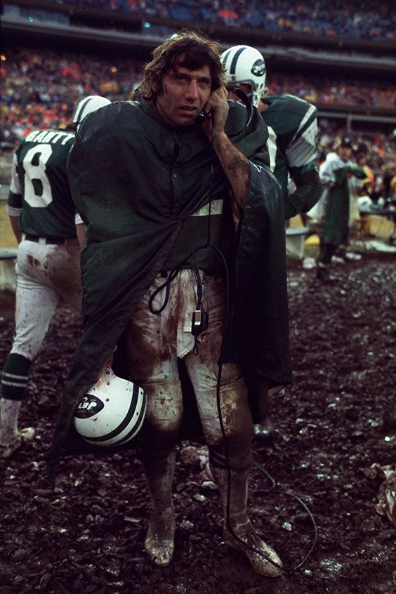 "Shea Stadium, Flushing, NY, November 24, 1974  The Jets were playing the Buffalo Bills, and the Bills' O.J. Simpson was only a few yards away from breaking the all-time NFL rushing record. My assignment was to focus on O.J. for the whole game. As it turned out, I ""got lucky"" and got a great picture of O.J.'s record-breaking run, which ran as the opening spread in Sports Illustrated that week. However, late in the game during a time-out, I turned towards the Jets bench. There was Joe Namath on the phone, perhaps twenty or thirty feet away from me. He was covered from head-to-toe in mud. Maybe he was just trying to ""get lucky"" after the game. I quickly forgot about O.J., turned my camera on Namath and shot until I had finished whatever number of frames were left in the camera. I knew I had a memorable picture the minute I took it."