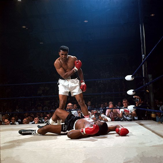 "St. Dominic's Arena, Lewiston, ME, May 25, 1965  Muhammad Ali KO'd Sonny Liston with one punch two minutes into the first round of their heavyweight championship fight in Lewiston, Maine. A two-minute fight is surely a major disappointment for fans who pay dearly for tickets, but for photographers, it really doesn't matter whether the fight lasts fifteen rounds or fifteen seconds. The first thing any picture editor looks for is a great picture of the final knockout. In Lewiston, that knockout happened exactly where I had hoped it would. I instantly knew that I was in the perfect spot on the apron when Liston went down. My only thought was, ""Stay right there, Sonny! Please don't get up!"" A sports photographer must get lucky enough to be in the right spot at the right time. Obviously that was the case in Lewiston on that night. What I'm proudest of is that on that night, I didn't miss."
