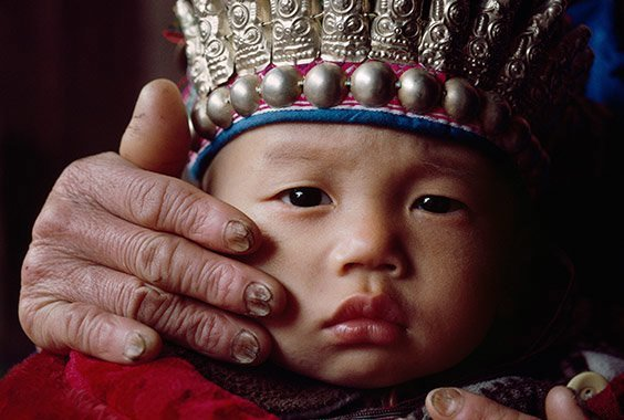 Quizhou, China Toughened by a lifetime of fieldwork, the hands of an elderly woman provide loving care for her grandson, who wears a traditional hat adorned in silver. With so many young adults working as migrant laborers, obliged to spend much of their time away in distant cities, the Dong have little choice but to leave childrearing in the hands of the elderly, creating in effect a culture without mothers or fathers.