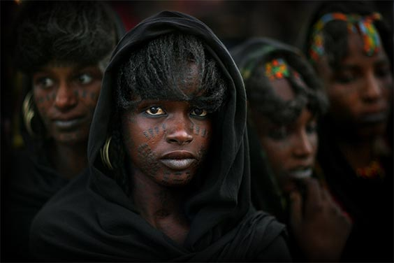 Near Lake Chad, Niger Among the Wodaabe, pastoral nomads of the sub-Sahara of Niger, charm and beauty are the most desirable character traits of both men and women. Here four women with traditional facial tattoos watch men dancing at the annual Geerewol festival.