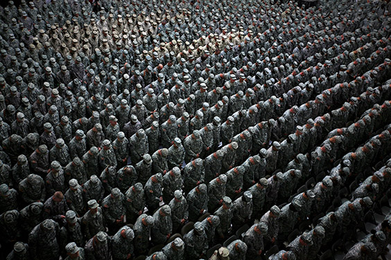 1,215 American soldiers, airmen, marines (patch of lighter uniforms in top left corner) and seamen (patch of lighter uniforms in top center) pray before the pledge of enlistment on July 4, 2008, at a massive re-enlistment ceremony in Al Faw palace in Baghdad, Iraq on July 4, 2008. (Photo by Ashley Gilbertson / VII Network)