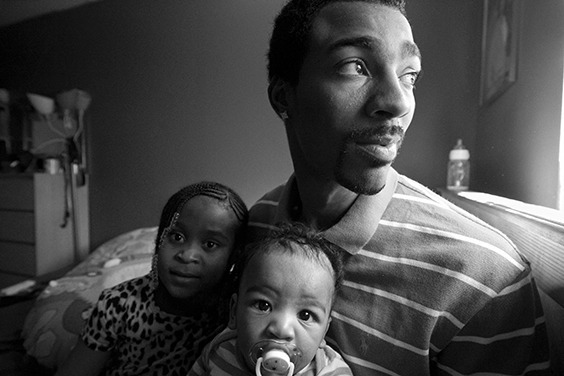 """Guy Miller relaxes in his bedroom with oldest daughter Nijeyah and newborn son Guy """"Chum"""" Jr. Bronx, NY, USA. October 2012. Portrait from the series Father Figure: Exploring Alternate Notions of Black Fatherhood."""