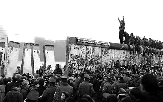 East Germans pour through the Berlin Wall in 1989 as a West Berliner cheers them on from atop.