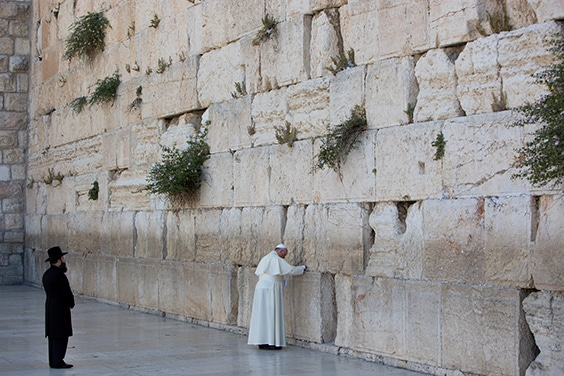 Pope Francis prays in front of the Western Wall, in Jerusalem's Old City, as Shmuel Rabinowitz, rabbi of the western wall stands by, Monday, May 26, 2014. Pope Francis has prayed at Jerusalem's Western Wall, the holiest place where Jews can pray, bowing his head as he touched the wall in the same gesture used a day earlier to pray at the Israeli barrier surrounding the biblical West Bank town of Bethlehem.