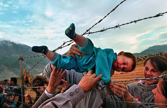 "In 1998, after a decade of increasing tension in Kosovo, violence by Serbian and Yugoslav forces against ethnic Albanians led to a wave of refugees fleeing the country. Sometimes separated families found each other; Carol Guzy captured such a moment at a United Arab Emirates-run camp in Kukes, Albania. Guzy recalled, ""It's actually a joyful photo. Families that had escaped ethnic cleansing did not know if their loved ones had survived or not; [they] were lined up along that fence.""  The Shala family from Prizren, Kosovo found each other at the fence and passed 2-year-old Agaim Shala through the barbed wire barrier so he could visit with his relatives.
