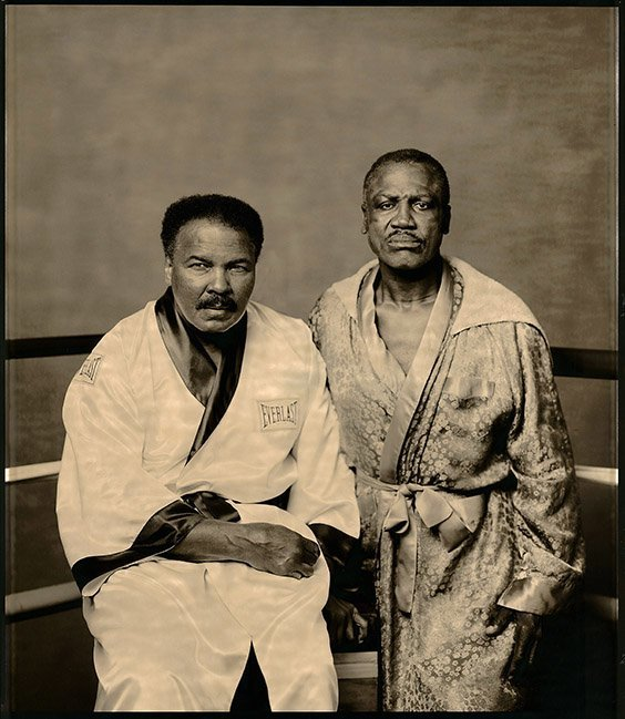 """Philadelphia, PA, 2003  It was easier to get Ali to pose for this picture than it was to get Frazier. Joe still resented all the torment Ali had caused him over the years. Joe finally agreed to pose when we offered to go to his gym in Philadelphia. There's not much I shoot at this stage of my career that puts me on edge. But this was one of those pictures that I knew would never happen again: the greatest rivalry in modern sports history. I wanted something unique, something monumental. I brought a 20x24 Polaroid camera and near the end they were hamming it up in every shot, I said, """"No, no. I don't want you to do anything. Just stare in the camera, no smiles, just stare."""" I did one frame, then a second, and there it was, the picture I was looking for: two battered warriors who'd left their lives in the ring."""