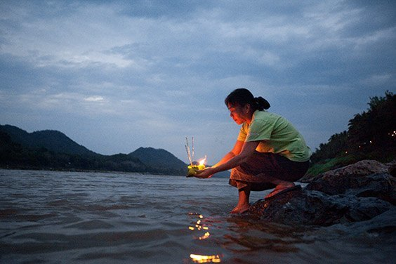 """Laos, 2009  A woman launches an offering on the Mekong River, known to Laotians as the """"mother of waters."""" The occasion is Boun Pi Mai Lao, the New Year's celebration, in April."""