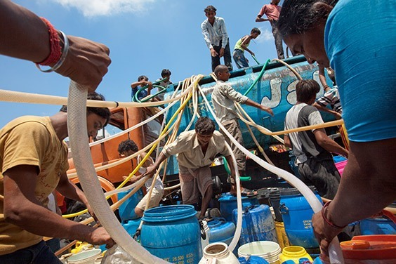 """India, 2009  In a parched Delhi slum, men swarm a tanker to siphon precious water. """"If you throw money here,"""" says a local 16-year-old named Vinay, """"no one would have time to grab it. Water is more important for us."""""""