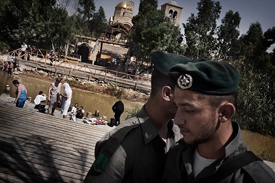 Israel, 2009  As pilgrims bathe and mill behind them, Israeli border police stand guard on the Jordan River's western bank. Over on the Jordanian side, churches and a tourist center commemorate the traditional site of Jesus's baptism.