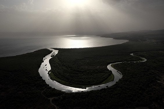 Israel, 2009  Shards of sunlight illuminate the Jordan River as it flows into the Sea of Galilee. The biblical stream's headwaters are to the north, near Mount Hermon. Its final destination is the Dead Sea, some 200 miles downstream from the point of origin.