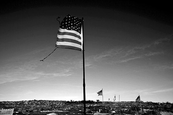 A torn American flag flies over a cemetery in Tuba, Arizona, where Thomasina Nez's former partner and father to five of her children is buried. The Bennett Freeze ban, instituted in 1966, prohibited home and property improvements on land in Arizona that was disputed by the Navajo and Hopi tribes. The law left 1.5-million acres frozen in bureaucracy until it was reversed in March 2009.