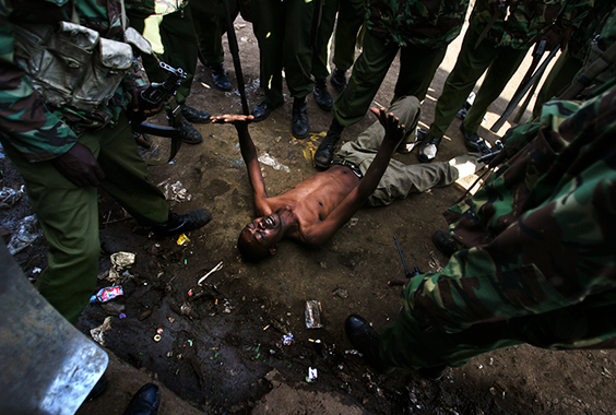 A man lays on the ground after being attacked by Kenyan police during clashes in the Kibera slums on January 17, 2008 in Nairobi, Kenya. Some 600 people have been killed in severe post-election violence amid allegations that the incumbent president manipulated the December elections.