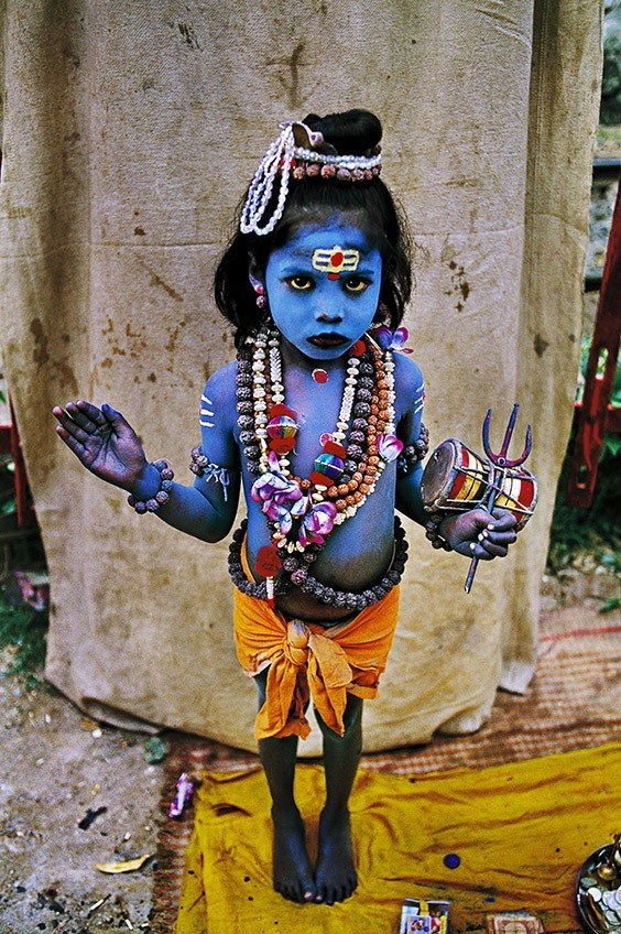 Haridwar, India  A young child dressed as the Hindu deity Lord Shiva, often depicted in the color blue, asks for money at a religious festival in Haridwar, India.