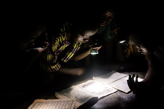 "From ""Life without Lights"" Children read the Koran by flashlight at a mosque in Wantugu, Northern Region, Ghana, 2007. Wantugu had power lines installed in 2000, but government officials failed to connect them to a power source. The series documents global energy poverty among some of the 1.4 billion people in the world who live without access to electricity."
